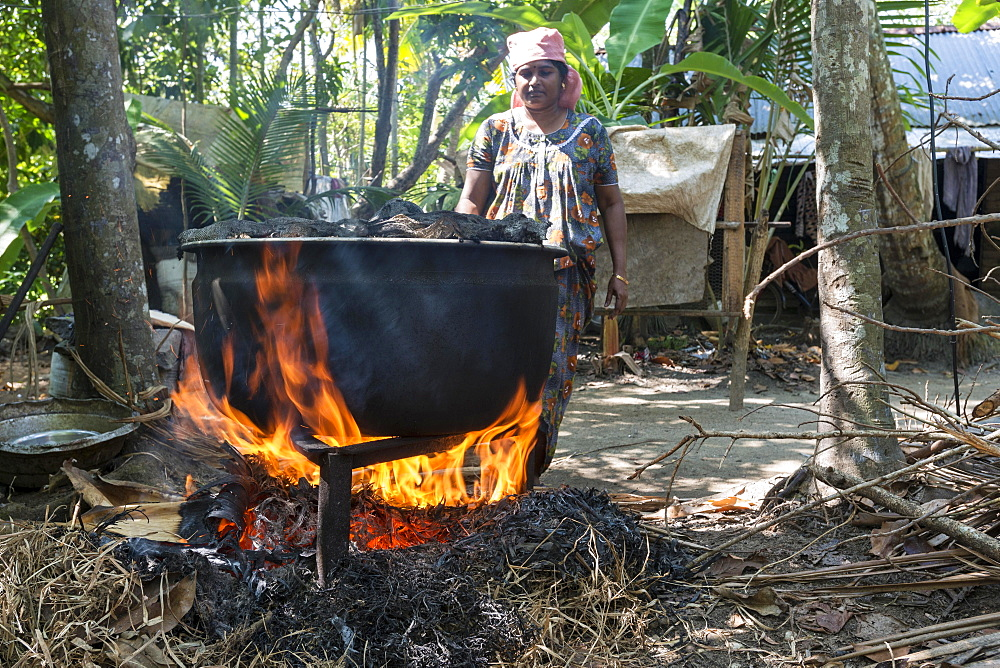 A woman cooking on open fire, Alappuzha, Kerala, India, Asia