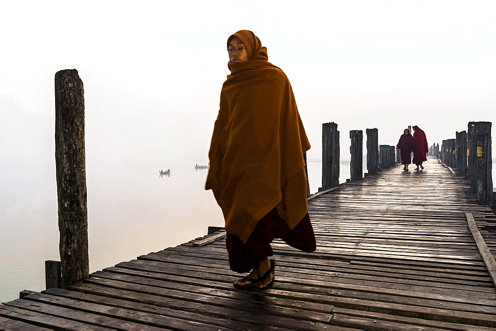 Monks walking on a teak bridge, U Bein Bridge, across Thaungthaman lake, in the morning, Amarapura, Mandalay Division, Myanmar, Asia