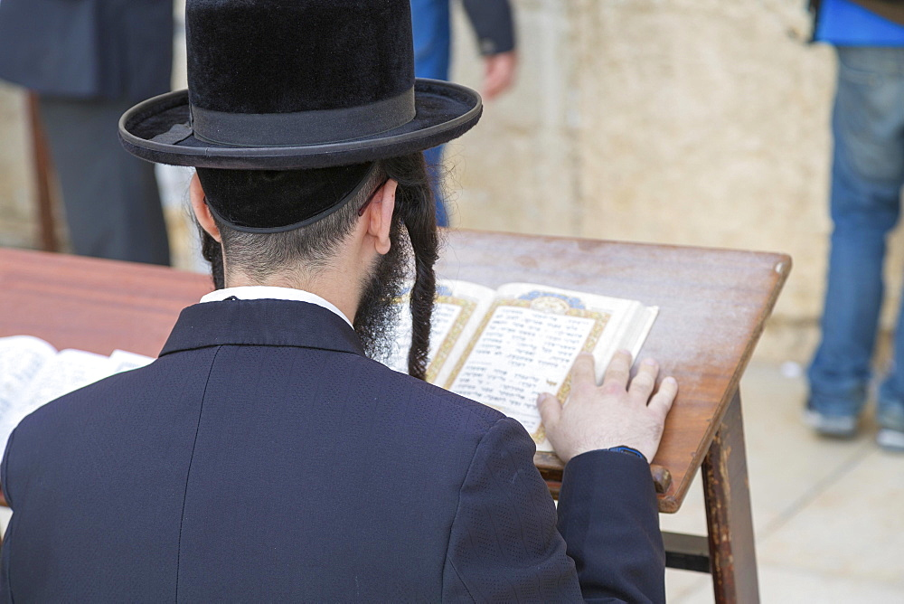 Ultra-orthodox Jew praying at the Western Wall, Wailing Wall, view over his shoulder onto the Talmud, Jerusalem, Israel, Asia