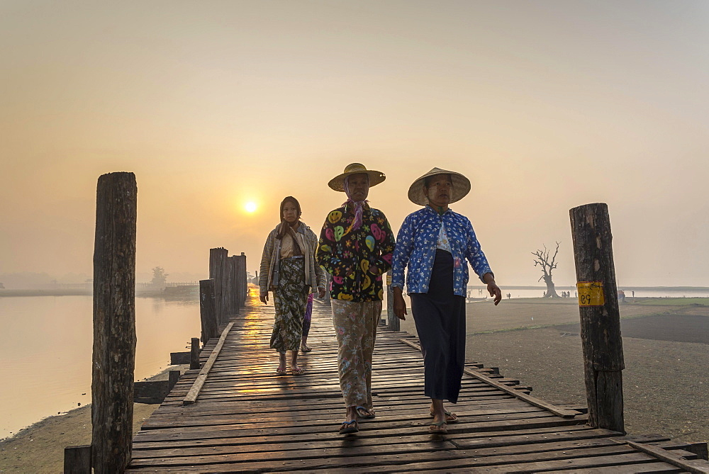 Women wearing traditional hats on a teak bridge, U Bein Bridge over Taungthaman Lake at sunrise, Amarapura, Mandalay Division, Myanmar, Asia