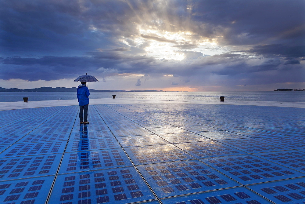 "Woman holding an umbrella, standing on the solar art installation """"Greeting to the Sun"""", Zadar, Dalmatia, Croatia, Europe - 832-383128"