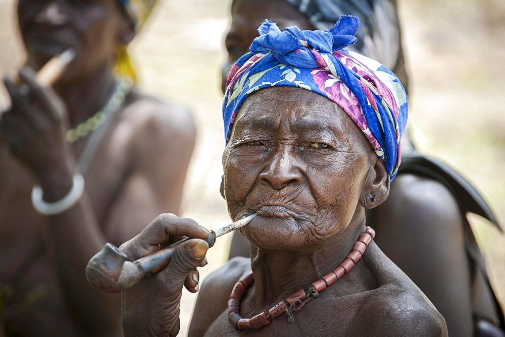An elderly woman from the Koma people smoking a pipe, the animistic people live in the Alantika Mountains, Wangai, North Region, Cameroon, Africa - 832-383254