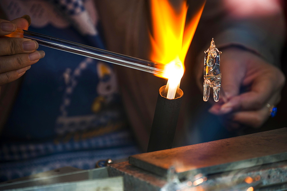 Glassblower working on a glass figure with a flame, Wuzhen, Zhejiang province, China, Asia