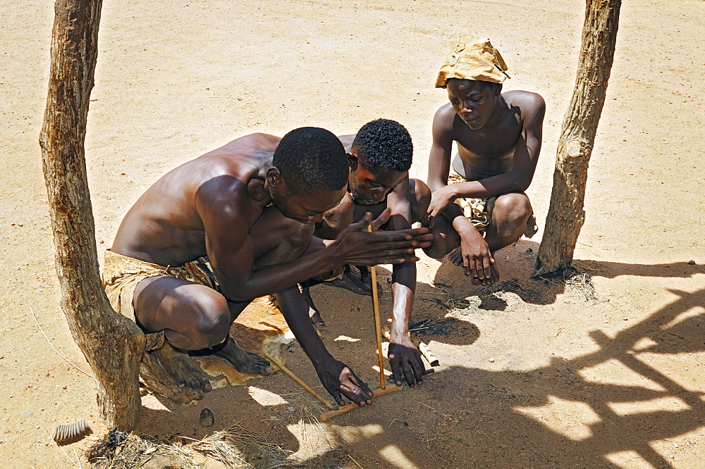 Three local men making fire, Damara Living Museum, near Twyfelfontein, Namibia, Africa