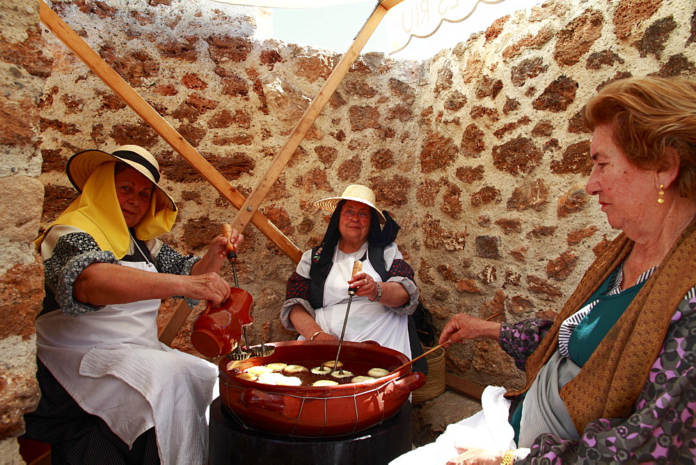 "Elderly women in traditional costume baking """"bunyols"""", typical fried dough balls, at a traditional handicraft fair, Ibiza, Spain, Europe"