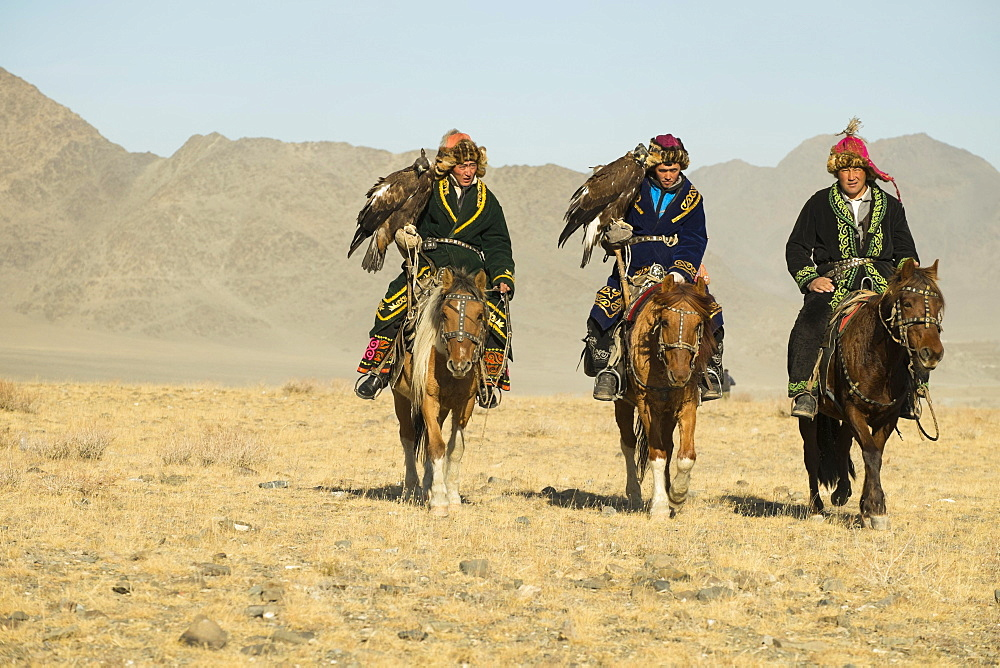 Three Kazakh eagle hunters on their horses on the way to the Eagle Festival in Sagsai, Bayan-Oelgii Aimag, Mongolia, Asia