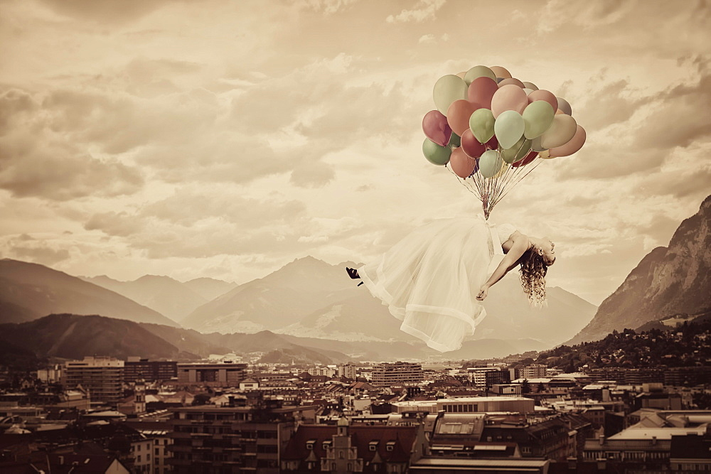 Bride floating on balloons over Innsbruck, Tyrol, Austria, Europe