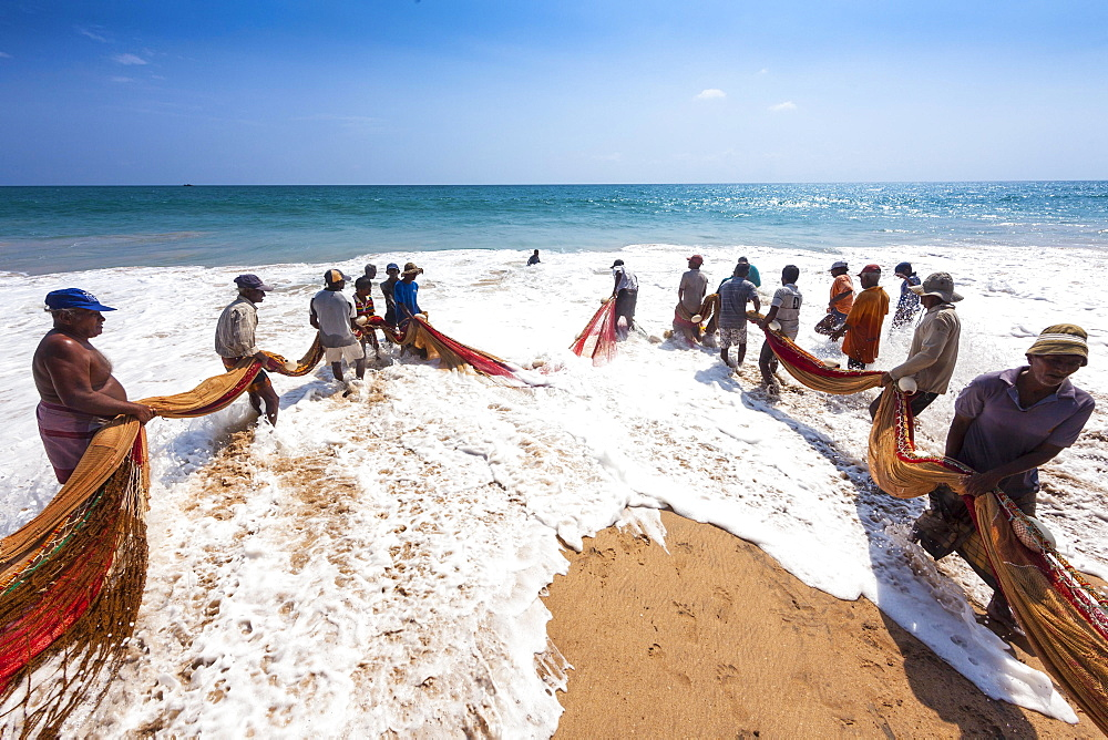 Fishermen, day labourers, hauling in a net on the beach, near Kottegoda, Southern Province, Sri Lanka, Asia
