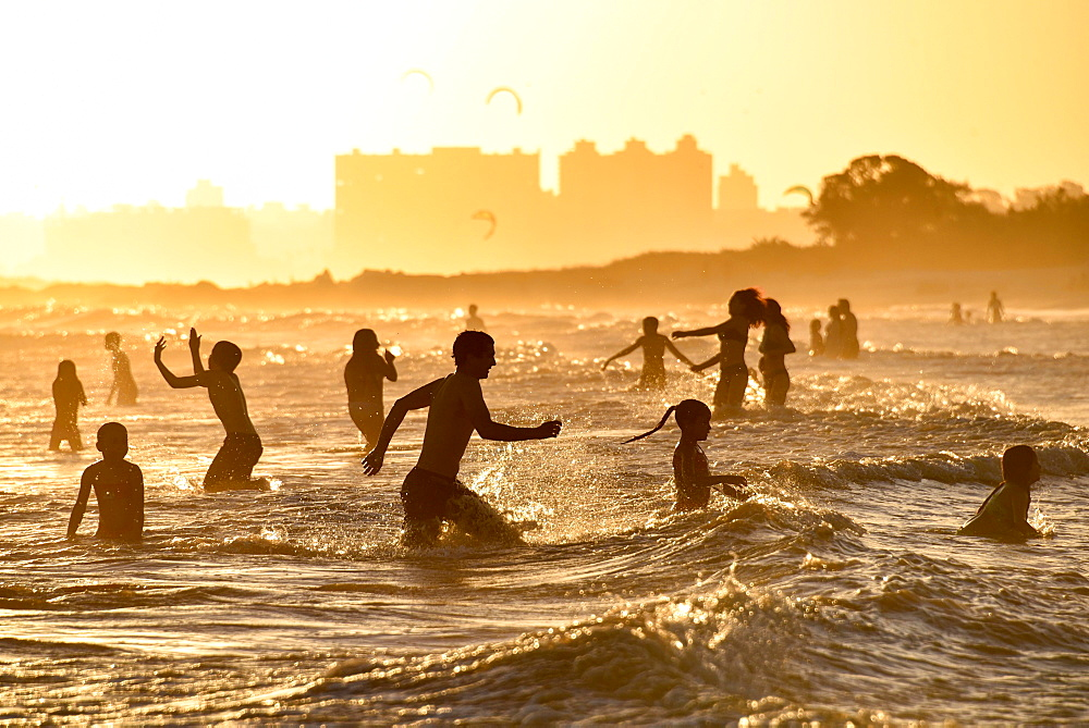 Many people bathing on the beach at sunset, beach Rambla, Montevideo, Uruguay, South America
