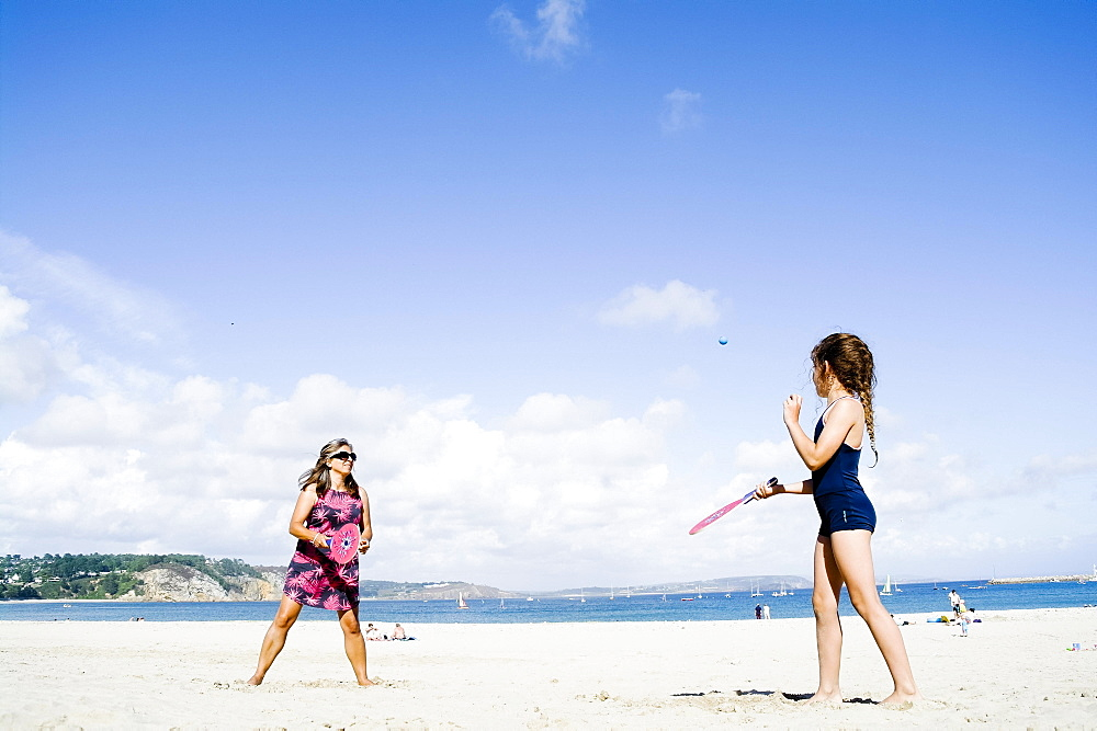 Mother and daughter playing beach bat and ball, Morgat, Brittany, France, Europe
