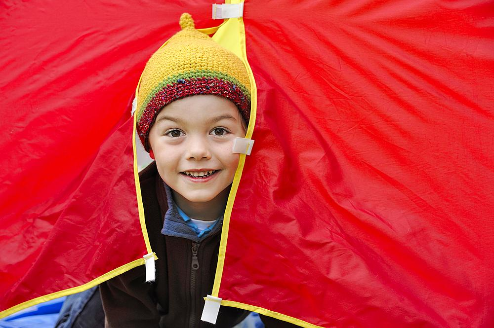 Boy with a knited cap looking out of a red tent, happy, Germany, Europe