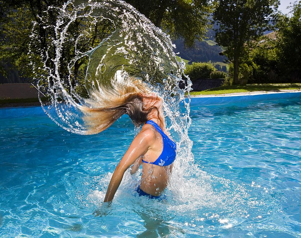 Woman emerging from a swimming pool, throwing up her hair and water into the air