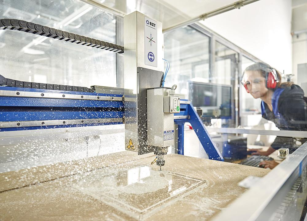 Woman with ear protection operates CNC milling machine, CNC machine, Austria, Europe - 832-383768