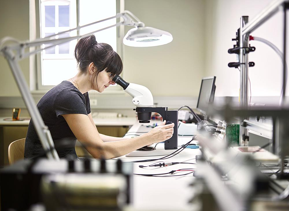 Technician, young woman using electronic microscope - 832-383770