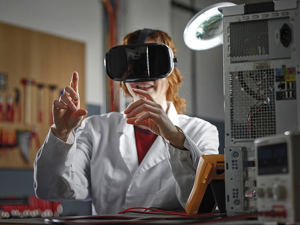 Woman with VR goggles and lab coat sitting in an electronics laboratory, Austria, Europe