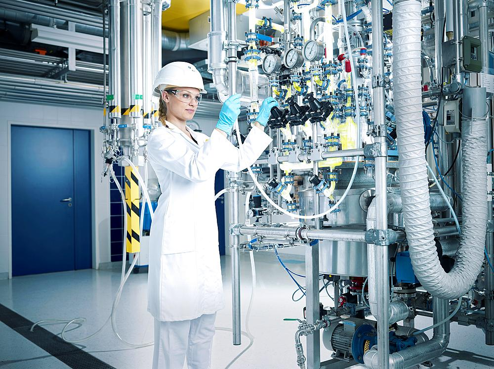 Chemielaborantin, chemist with helmet and goggles in a pharmaceutical production, Austria, Europe