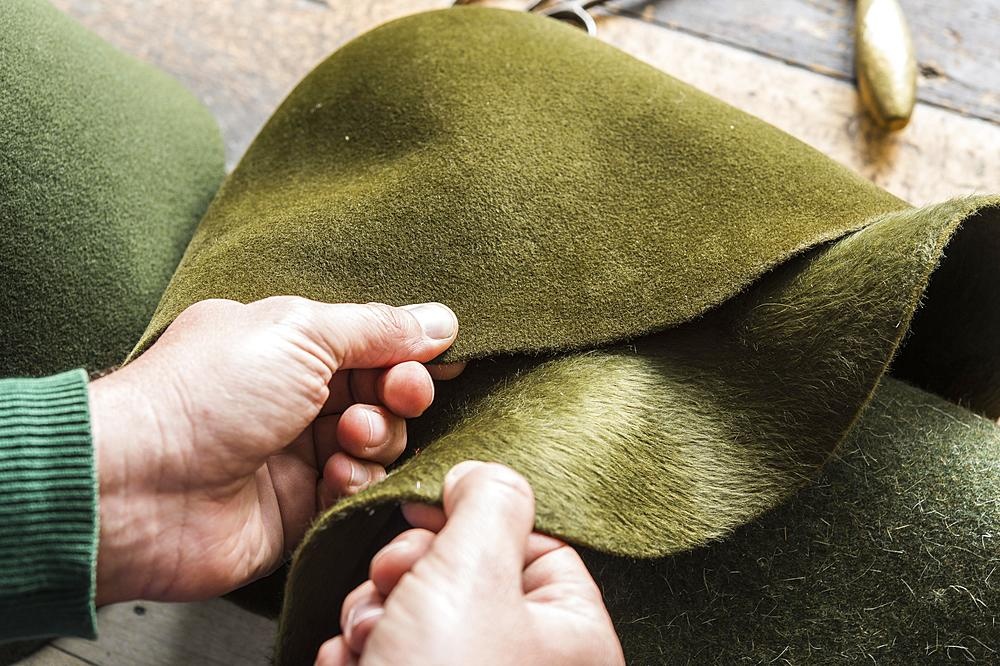 Hands checking different wool felt hat bodies, shades of green, on workbench, hatmaker workshop, Bad Aussee, Styria, Austria, Europe