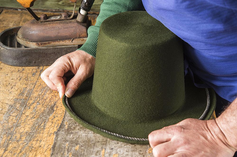 Hands holding cord on dry wool felt hat with shaped edge, hatmaker workshop, Bad Aussee, Styria, Austria, Europe - 832-383793