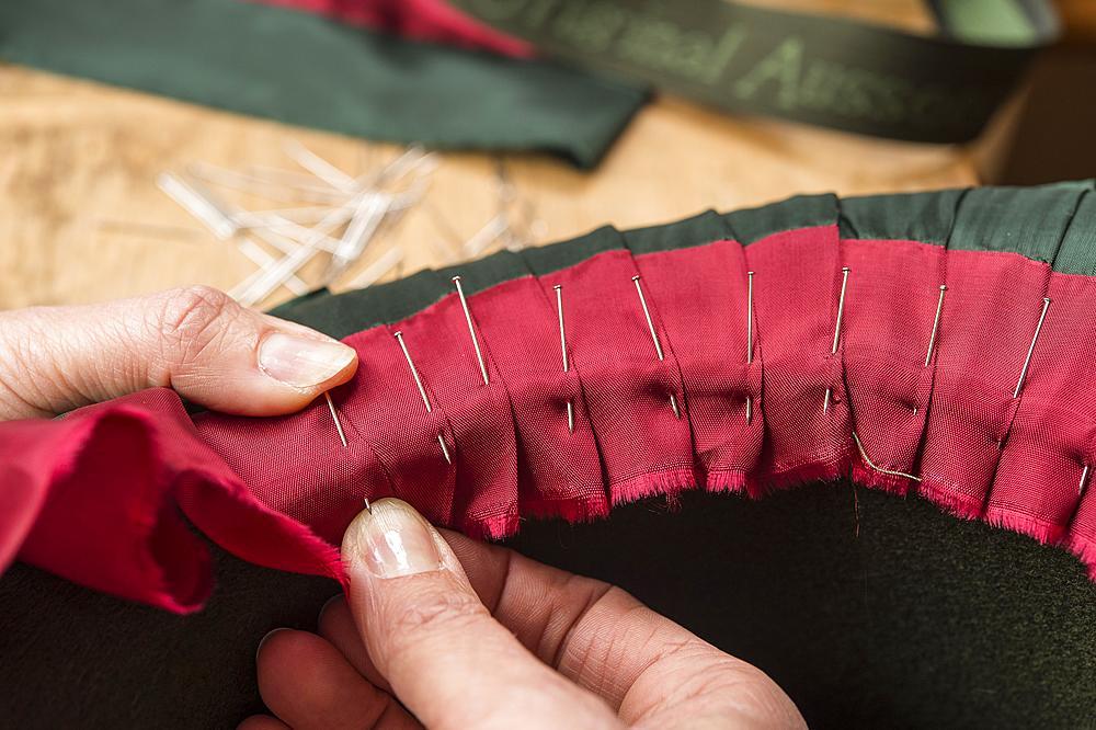 Hands folding and fastening silk ribbon using pins, inner lining of a wool felt hat, hatmaker workshop, Bad Aussee, Styria, Austria, Europe - 832-383796
