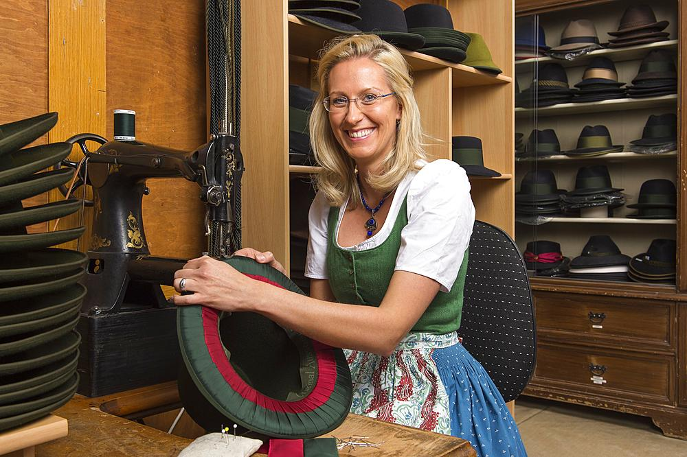 Woman sewing silk ribbon and inner lining on hat edge, finished hats on shelves behind, hatmaker workshop, Bad Aussee, Styria, Austria, Europe - 832-383797