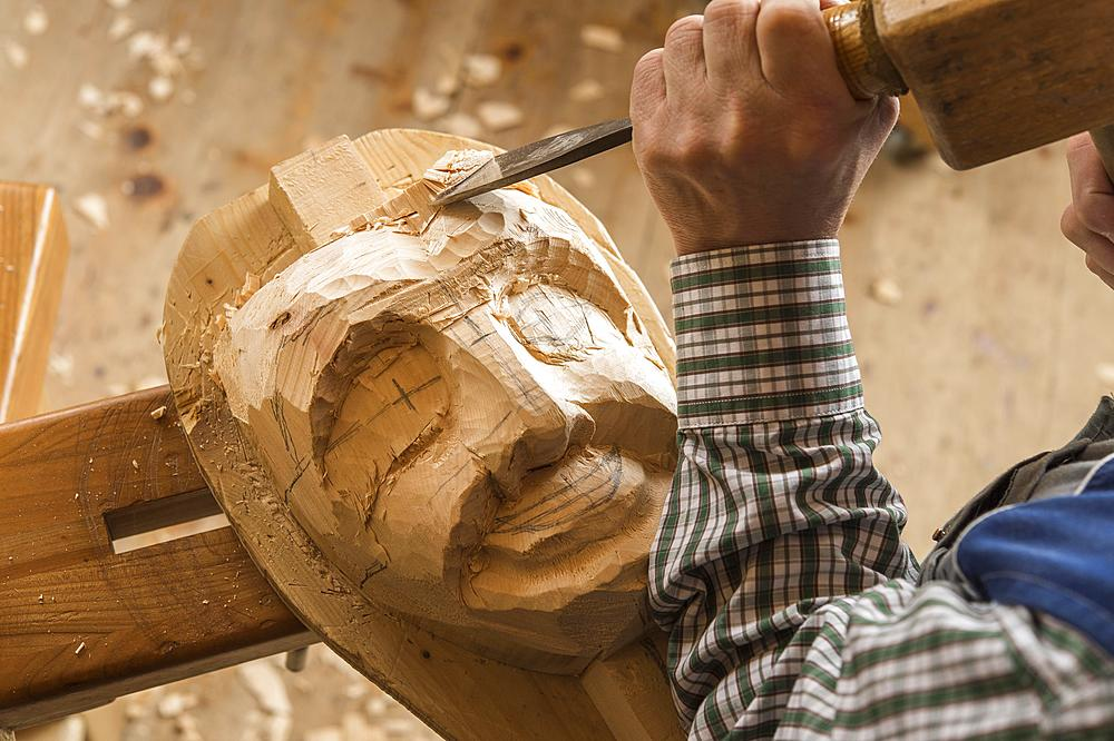 Carving the face of a wooden mask into wooden block using wood carving tools, wooden mask carver, Bad Aussee, Styria, Austria, Europe
