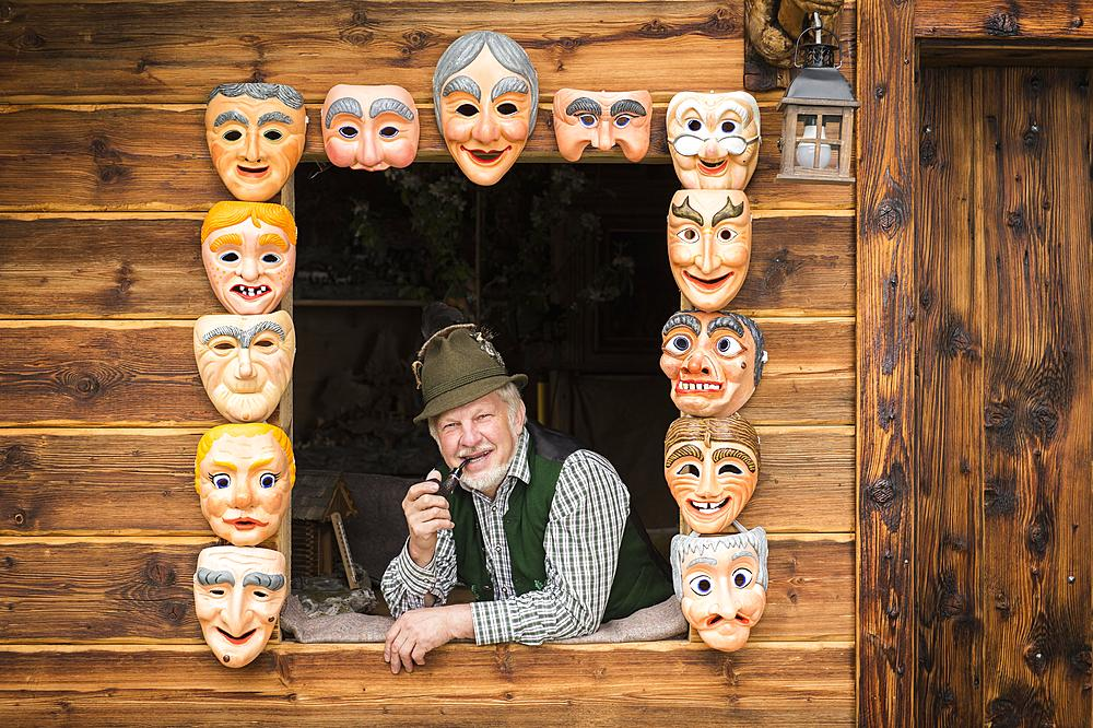 Wooden mask carver in a window, framed by painted wooden masks, wooden mask carving workshop, Bad Aussee, Styria, Austria, Europe