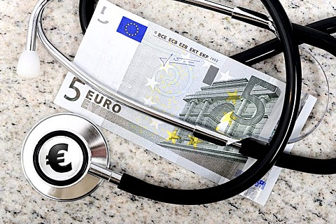 Doctor's stethoscope and a five euro banknote, symbolic image for the payment of five euro per doctor visit