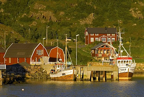 Typical red Rorbuer huts, rorbu, and boats illuminated by warm evening light near Straume on the island of Langoya, Langoya, part of the VesterÂlen, Vesteralen archipelago, Nordland, Norway, Europe