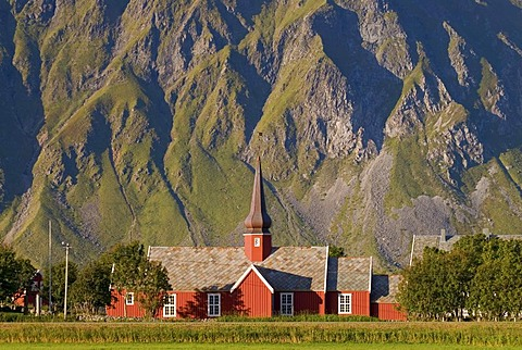 The red stave church of Flakstad in front of steep mountains, Vareid, Fredvang, island of Flakstadoya, Flakstadoya, Lofoten archipelago, Nordland, Norway, Europe