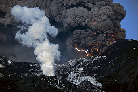 A flash of lightning in the ash cloud from the Eyjafjallajoekull Volcano while it ejects magma, lava flow in front of the glacier producing a water vapor cloud, Eyjafjallajoekull, Iceland, Europe