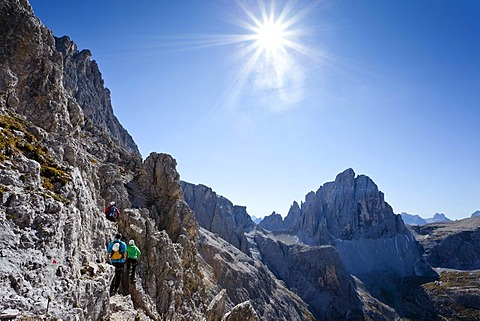 Hiker ascending the Alpinisteig climbing route, currently on Elferscharte Mountain, looking towards Zwoelferkofel Mountain, Alta Pusteria, Sesto, Dolomites, Alto Adige, Italy, Europe