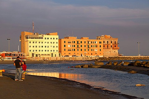 Young couple alone on the deserted beach front of Anzio, in evening light, Lazio, Italy, Europe