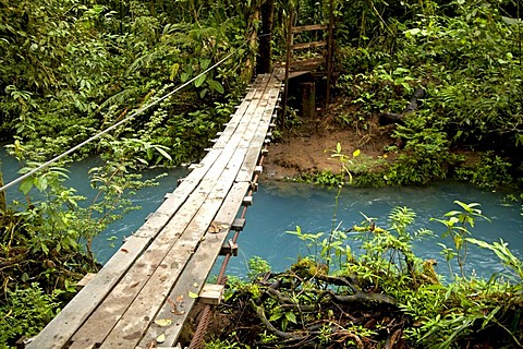 Suspension bridge over the blue waters of the Rio Celeste in Volcan Tenorio National Park, Costa Rica, Central America