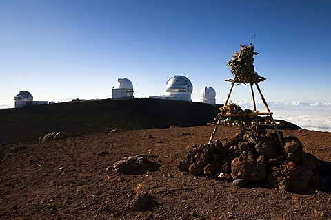 Hawaiian temple on the summit of the Mauna Kea Volcano, 4205m, part of the Mauna Kea Observatory on the horizon, Mauna Kea, Hawai'i, USA