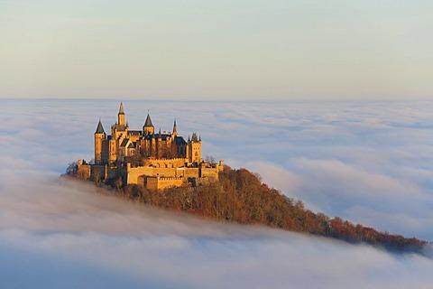 Burg Hohenzollern castle in morning light with autumn forest, morning mist, Schwaebische Alb, Swabian Alb, Baden-Wuerttemberg, Germany, Europe
