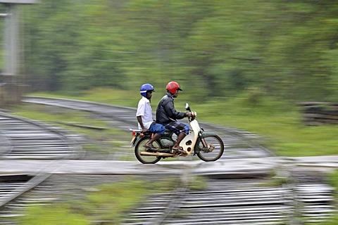 Moped riders in heavy rain, railway crossing in Kalawewa, Sri Lanka, Ceylon, South Asia, Asia, PublicGround