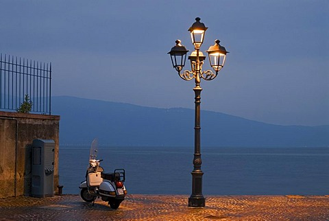 A Motorino scooter beside a street lamp at the shore of Lake Garda at the blue hour in Gargnano, Lombardia, Italy, Europe