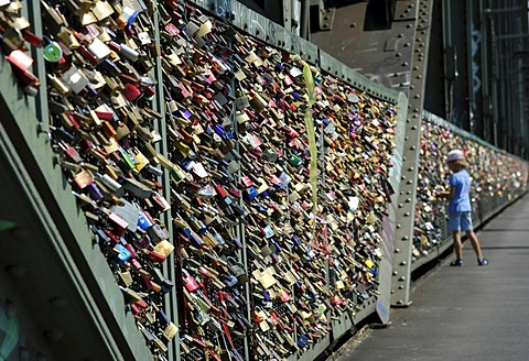 Love padlocks on security grid that separates the footpath from the railway tracks on Hohenzollern Bridge, Cologne, North Rhine-Westphalia, Germany, Europe