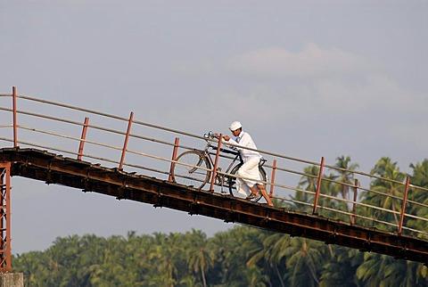 Man walking his bike on a bridge across the Backwaters, Nileshwaram, Malabar Coast, northern Kerala, Kerala, southern India, India, Asia