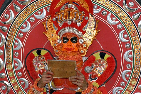Theyyam performer looking into a mirror, moment of initiation, during a Theyyam ritual, near Kasargod, North Kerala, South India, Asia