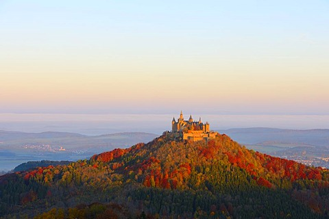 Burg Hohenzollern Castle in the early morning light with autumnal forest, early morning fog, Swabian Alb, Baden-Wuerttemberg, Germany, Europe