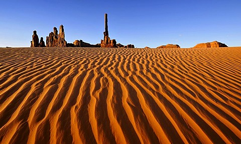 Sand dunes in front of Totem Pole and Yei Bi Chei rock formations after sunrise, Monument Valley, Navajo Tribal Park, Navajo National Reservation, Arizona, Utah, USA
