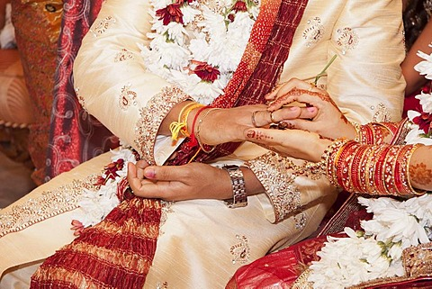 Indian bride passing wedding ring on her groom's finger