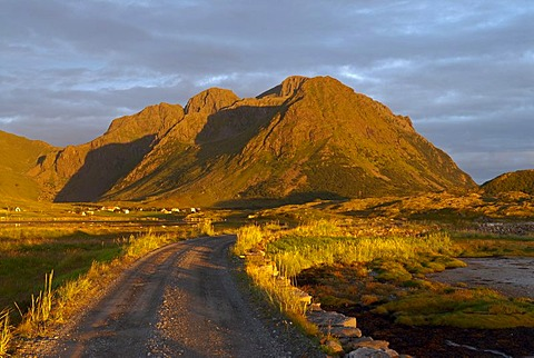 A gravel road winding towards a steep mountain illuminated by warm evening light in Sandoya, Nordland, Norway, Europe