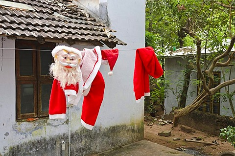 Santa Claus costume drying on a laundry line after Christmas time in Varkala, Kerala, India, Asia