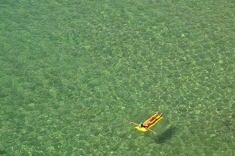 Woman on a lilo, Playa Levante beach, Benidorm, Costa Blanca, Spain, Europe