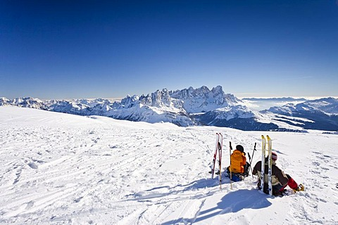 Cross-country skiers taking a break on the summit of Uribrutto Mountain above the Passo Valles, looking towards the Palla Group and the Rolle Pass, Trentino, Dolomites, Italy, Europe