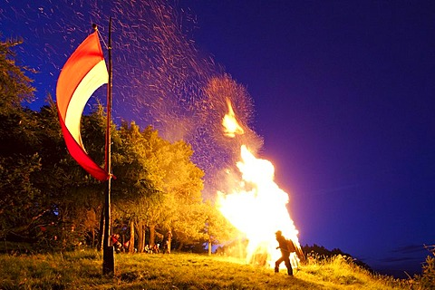 Fire on Kleiner Penegal mountain above Kaltern, Sacred Heart-Fire, with the flag of Tyrol, province of Bolzano-Bozen, Italy, Europe