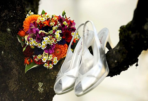 Bridal bouquet and silver wedding shoes hanging from a tree