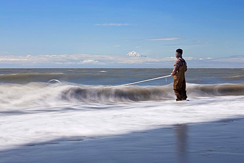 Surf zone with a fisherman on the beach in Kenai on the Kenai Peninsula with Mount Redoubt volcano in the Cook Inlet, Alaska, USA